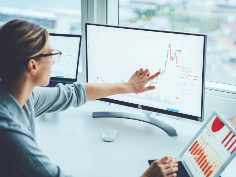 Sellerdeck Business woman study financial market to calculate possible risks and profits.Female economist accounting money with statistics graphs pointing on screen of computer at desktop. Quotations on exchange